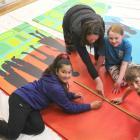Rimu Full Primary School principal Kate Webster overlooks artist Jemima Pedro working with pupils...