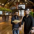 Al Sultan restaurant owner Mohammad Saad Aldeen holds some baklava while standing alongside his...