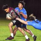 Bears player Chey Grace takes the ball up while University players Aiden Mwaahi (centre) and...