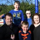 Matt Paterson dons a GPSOS pendant at a Dunedin playground with his sons (from left) Archie (6),...
