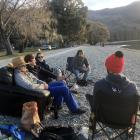 Watching the sun set from the Lake Wanaka foreshore on Saturday are (from left) Leo Bananche (23)...