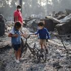 Children look at a burned bicycle after wildfires destroyed a neighbourhood in Bear Creek,...