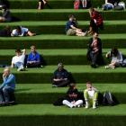 People are seen relaxing in an outdoor seating area while social distancing in London. Photo:...