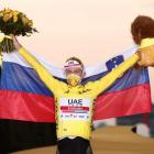 Tadej Pogacar celebrates his victory on the podium. Photo: Reuters