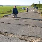 Peter Fitzgerald, left, and his brother Rex, stand in cracks where Highfield Rd was lifted and...