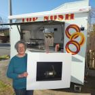 Jean Bonsor in her Top Nosh food trailer holds a signed copy of Grahame Sydney's eponymous work....