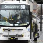 A bus driver explains the use of the new Bee Card to a passenger as another waits to board in...
