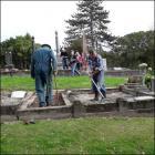 Volunteers repairing headstones and graves in Akaroa. Photo: Supplied