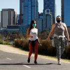 People in masks are seen exercising along the Yarra River in Melbourne yesterday. Photo: Getty
