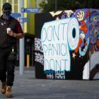 A man in a mask walks past street art in Prahran, in Melbourne. Photo: Getty