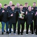 The Southern Premier League champion Green Island football team gathers with the trophy before...