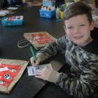 Ollie Yio (9) enjoys his holiday colouring his ''global passport''.
