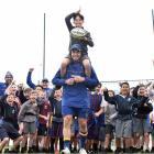 Josh Thompson (10), of St Bernadette's School, is carried on the shoulders of Otago midfielder...