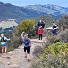 Paula Brown (centre), of Bluff, does an impromptu Highland fling at the peak of Mt Cargill in...