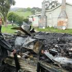 Kaitangata resident Christine Tucker inspects the destruction from a shed fire close to her...