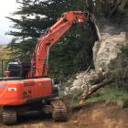 An excavator equipped with a rock-breaking attachment breaks up a large unstable boulder that...