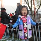 Nancy Wu (4) waves the Chinese flag during a celebration of the 71st anniversary of the founding...
