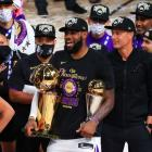 LeBron James celebrates with the NBA and Finals MVP trophies with the Los Angeles Lakers...