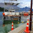 Workers in wetsuits set up a temporary structure at the Queenstown waterfront in ...