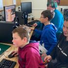 Young computer fans Daniel Hill (9, at front) and Ethan Wright (12) work on technology problems...