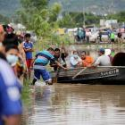 People take to boats in floodwaters during the passage of Storm Eta, in Pimienta, Honduras. Photo...