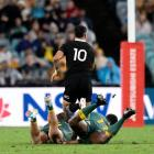 Richie Mo'unga breaks the tackles of Wallabies Michael Hooper and Marika Koroibete in Sydney last...