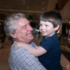 Sydney grandad Alan Kinkade hugs his grandson Tom, who lives in Melbourne, upon meeting at Sydney...
