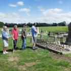 Some local residents observe a blessing and prayer ceremony at Drybread Cemetery on Monday,...