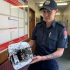 Invercargill Firefighter Tianna Newlove holds a fan heater which caught fire at a property she...