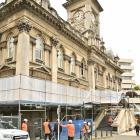 Staff from Brazier Scaffolding work outside the Municipal Chambers in the Octagon, Dunedin, to...