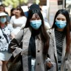 People wear face masks on a street in Melbourne. Photo: Getty