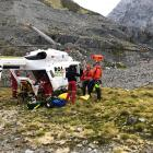 An injured climber is put into a helicopter after being lowered to a safe location and receiving...