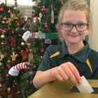 Emma Corson (9) votes for her favourite Christmas tree after admiring the 14 on display at...