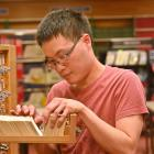 Volunteer Peter Lim with the Dunedin City Library's collection of old newspaper index cards....
