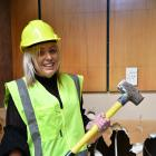 Southland Charity Hospital board trustee Melissa Vining wields a sledgehammer on Monday. PHOTO:...