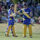 Llew Johnson acknowledges the crowd as Mitch Renwick congratulates him after he scored 50 runs...