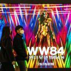 People wearing masks walk past an advertising billboard of the movie 'Wonder Woman 1984'. Photo:...