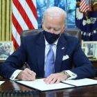 New US President Joe Biden signs executive orders in the Oval Office of the White House after his...