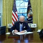 Joe Biden signs executive orders in the Oval Office of the White House in Washington, after his...