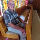 Carl Ruddenklau with two of the church pews that are now surplus to requirements. Photo: Supplied