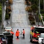 Firefighters cordoned off Baldwin St, in Dunedin, yesterday ...