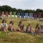 Glastonbury festival goers sit under a large sign on one of the hills.
