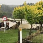 A tractor driver attempts to pull out a debris-covered fence near Pyramid Bridge after floods...