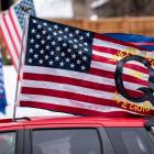 A car with a flag endorsing the QAnon drives by as supporters of President Donald Trump gather...