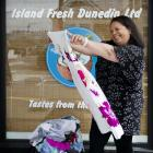 Island Fresh Dunedin owner Regina Khan sorts through some of the children's clothing that is to...