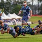 Hurricanes lock Jordie Barrett is caught in the tackle by Shannon Frizell of the Highlanders in a...