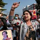 Demonstrators hold placards with the image of Aung San Suu Kyi during a protest against the...