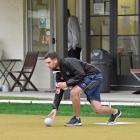 Elliot Mason delivers a bowl while Keanu Darby watches at the Wakari Bowling Club on Wednesday...