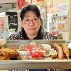 East Taieri Dairy and Takeaways owner Crystal Cao with a tray of food, typical of what she has...