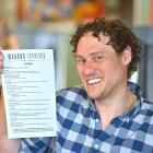Modaks Espresso owner Jack Bradbury with his cafe's new menu which has been translated into te...